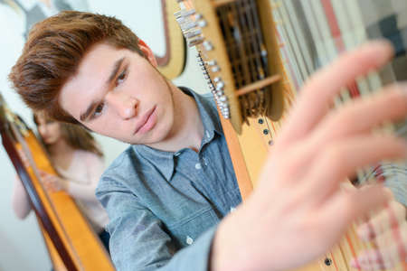 pluck: Teenager playing the harp Stock Photo