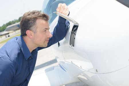 flap: Man looking through open flap on aircraft