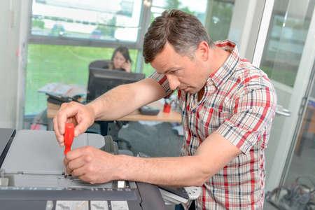 xerox: Man repairing photocopier