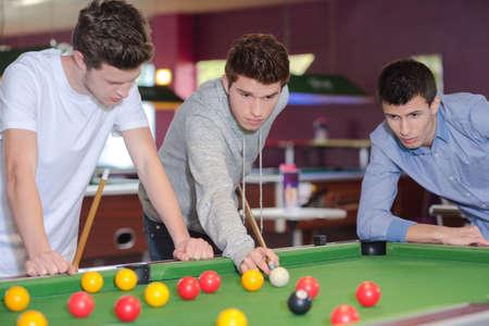billiards hall: Three men around the pool table Stock Photo