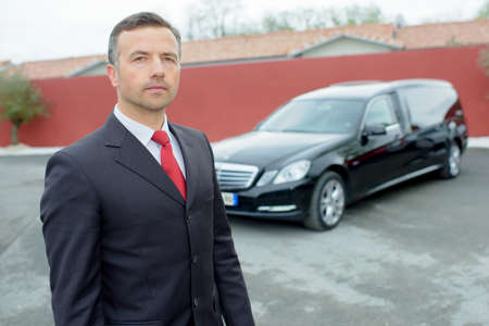 mortician: Portrait of funeral director in front of hearse