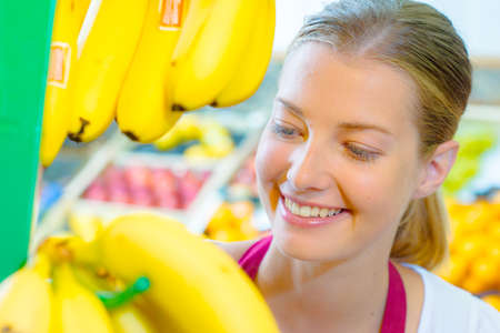 shop assistant: Shop assistant checking bananas