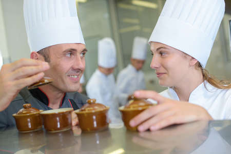 ramekin: Two chefs smiling and holding ramekin pots
