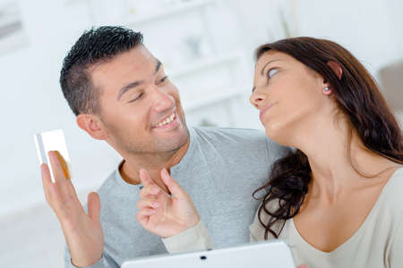withhold: Couple on computer, man holding credit card Stock Photo