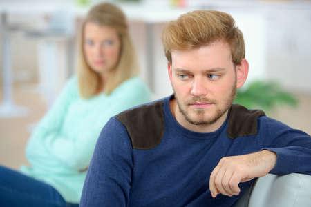 sulking: Couple sulking on a sofa