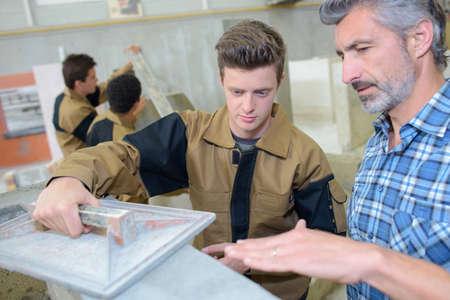 leveler: Man teaching apprentice to float cement