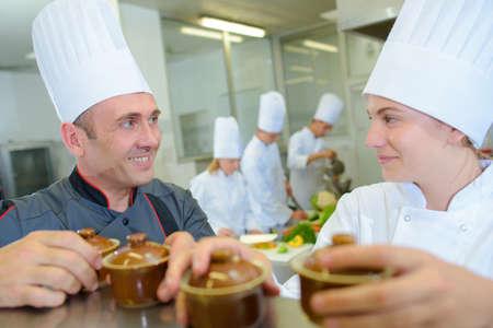 ramekin: Chef and trainee holding ramekin pots Stock Photo