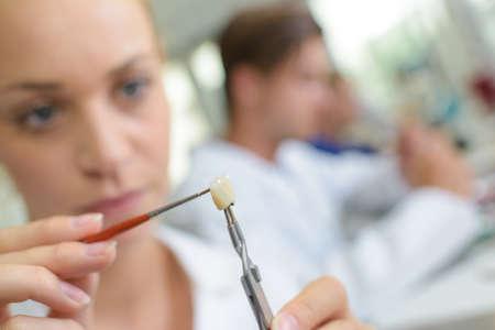 Weibliche Zahntechniker auf einzelne Zahn Arbeits