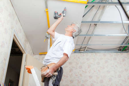 putting up: Builder putting up a suspended ceiling