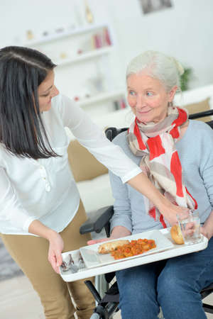 disabled person: Giving old lady her lunch