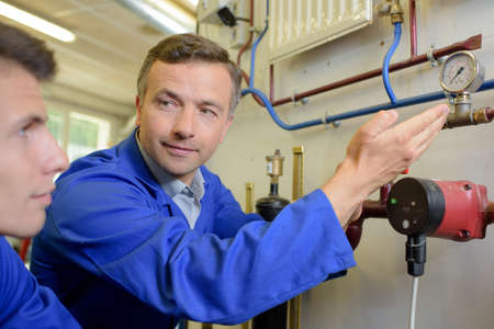 tradesman: Tradesman showing apprentice an inline dial
