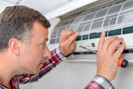 ventilate: Man setting up an air conditioning unit Stock Photo