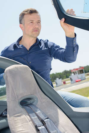 company person: Man entering cockpit of aircraft