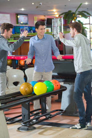 poised: Young men bowling, poised to high five Stock Photo