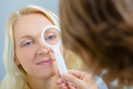 doctor giving glass: lady having eye examination Stock Photo