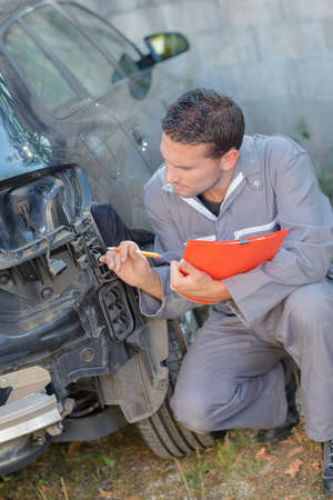 attractive charismatic: Mechanic inspecting damaged car Stock Photo