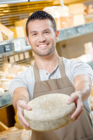 shop assistant: Shop assistant holding cheese