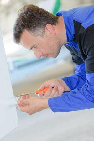 tradesman: Tradesman using screwdriver on boiler