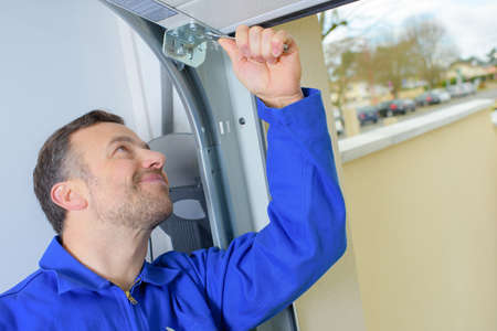 Man installing a garage door Stock Photo - 57970162