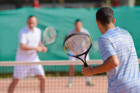 serf: Men playing doubles game of tennis