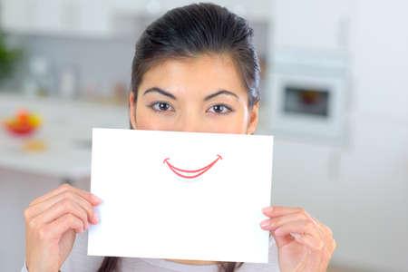 la boca: Mujer que sostiene la hoja de papel sobre su boca