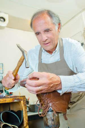 hammering: Cobbler hammering sole of boot
