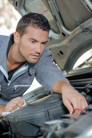 refurbish: Man fixing a car engine Stock Photo