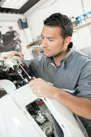 tornillos: Mecánico que trabaja en scooter