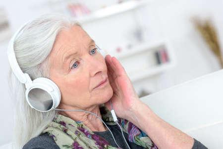 señora mayor: La señora mayor con los auriculares puestos