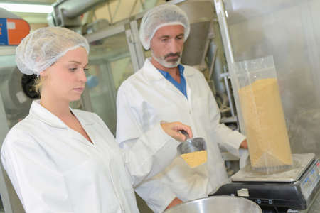 supervision: Man and woman weighing ingredient into bag Stock Photo