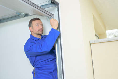 Man fixing a garage door Фото со стока - 58327055