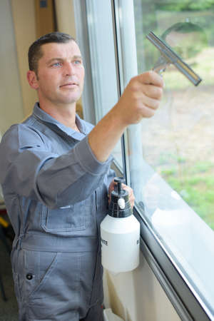 pressurized: Man cleaning window with squeegee Stock Photo