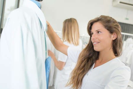 dry cleaner: girl choosing shirt Stock Photo