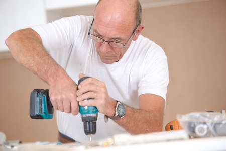 wooden surface: Carpenter drilling into a wooden surface