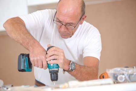 menuisier: Carpenter forage dans une surface en bois