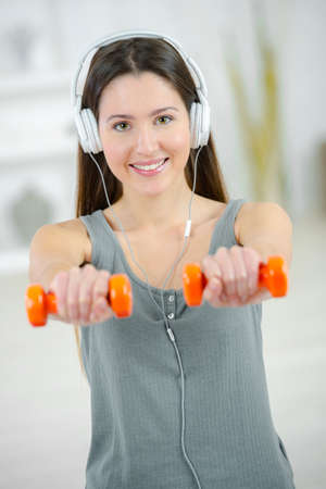 whilst: Woman lifting weights whilst listening to music