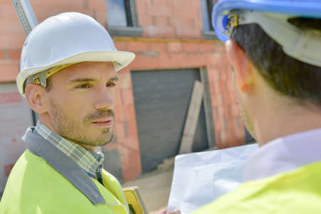 taskmaster: Two building designers chatting on site Stock Photo
