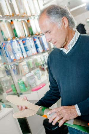 buying shoes: Hombre mayor compra reemplazar las suelas de sus zapatos Foto de archivo