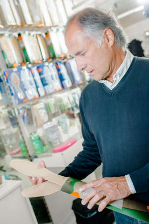 replace: Senior man buying replace soles for his shoes Stock Photo