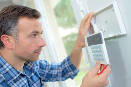 intrusion: Electrician fitting an intrusion alarm