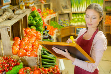 veg: Woman writing sign for fruit and veg Stock Photo