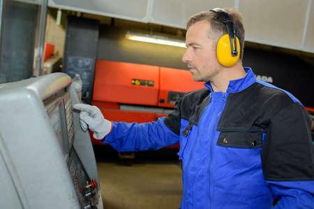 boilersuit: Man wearing ear protectors using machine