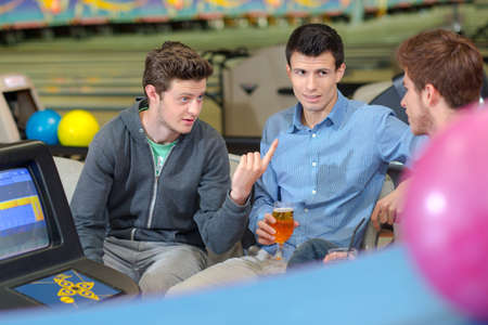 chums: Three friends in bowling alley, chatting