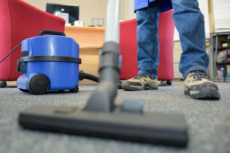 floor level: View of vacuum and feet at floor level Stock Photo