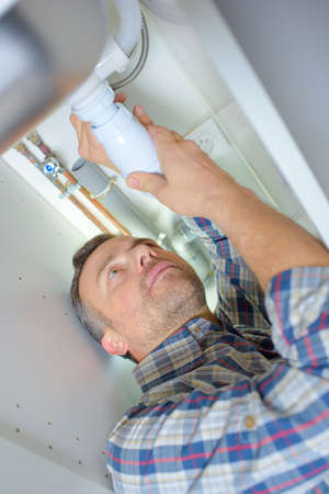 kunststoff rohr: Plumber working on a plastic pipe