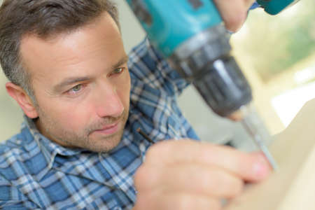 mounting holes: Carpenter carefully drilling a hole