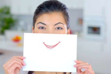 mouth smile: Woman holding sheet of paper over her mouth