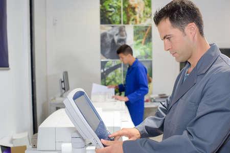 high quality: Man using control pad on printer Stock Photo