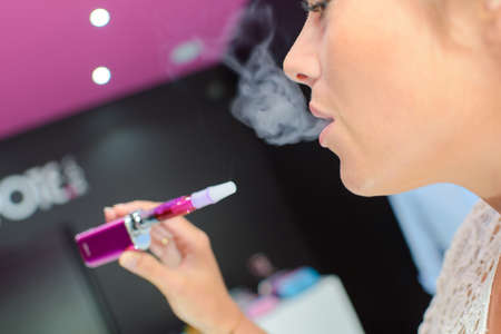 puffing: woman puffing an e-cigarette Stock Photo