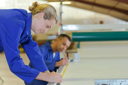 craftswoman: Workers marking measurements on material Stock Photo